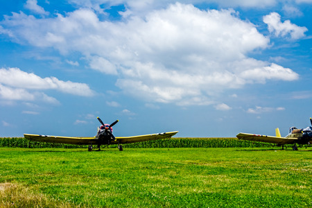 Old crop dusters lined up at airfield on green grass at sunset. photo