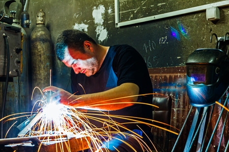 Welder is welding without protection in short sleeve shirt.