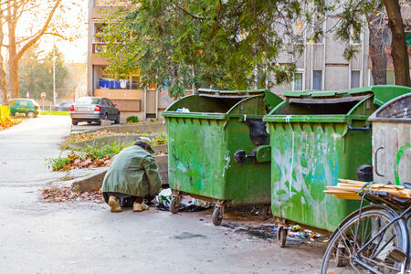 Homeless man with his bike investigates garbage. Stock Photo