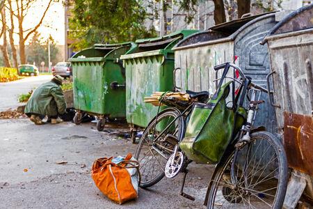 Homeless man with his bike investigates garbage. Banco de Imagens