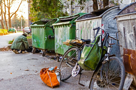 investigates: Homeless man with his bike investigates garbage. Stock Photo