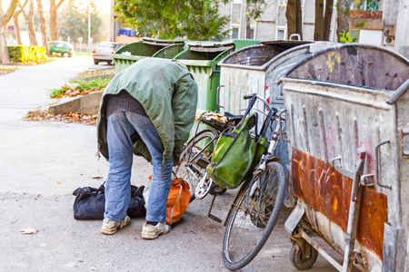 pauperism: Homeless man with his bike investigates garbage. Stock Photo