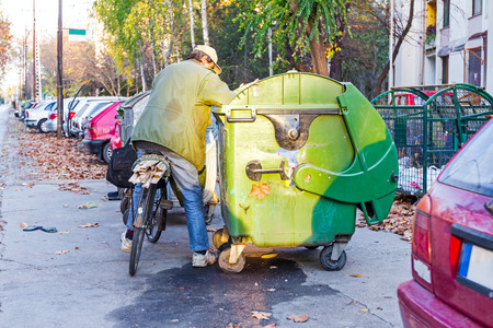 Homeless man with his bike investigates garbage. Banco de Imagens