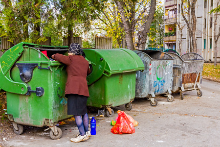 pauperism: Homeless woman is searching for food in garbage dumpster. Woman in poverty is searching something in container.