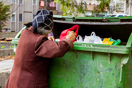 urban scenes: Homeless woman is searching for food in garbage. Woman in poverty is searching something in container.
