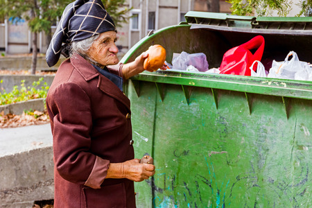 pauperism: Homeless woman is searching for food in garbage. Woman in poverty is searching something in container.