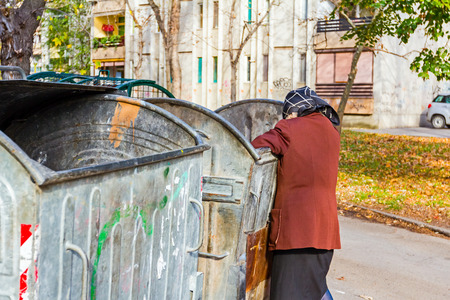 Homeless woman is searching for food in garbage. Woman in poverty is searching something in container.