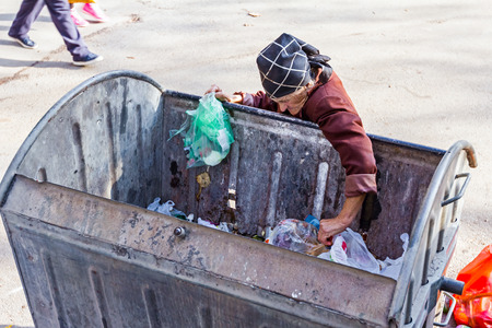 clustered: Homeless woman is searching for food in garbage. Woman in poverty is searching something in container.