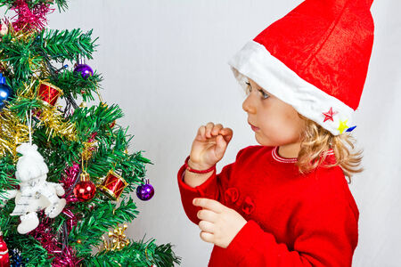 wearing santa hat: Portrait of a lovely little girl who is wearing Santa hat, she is standing against the Christmas background. Stock Photo