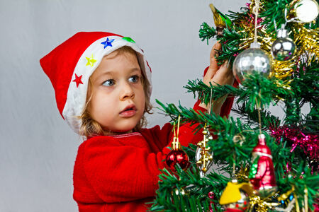 Portrait of a lovely little girl who is wearing Santa hat, she is standing against the Christmas background. photo