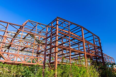 long lasting: Old rusty abandoned industrial structure with beams and vegetation growing on it with a melancholic look suggesting long lasting work. Stock Photo