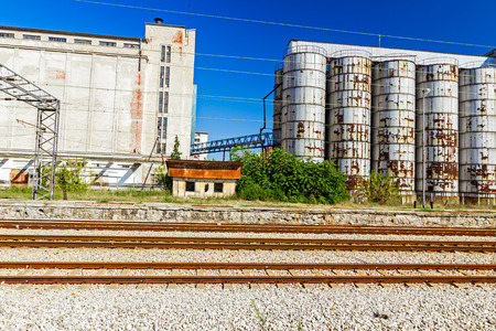 Industrial Silo, in background, behind parallel railroad tracks.