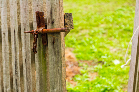 Old wooden fence with an open gate door has a rusty iron handle photo