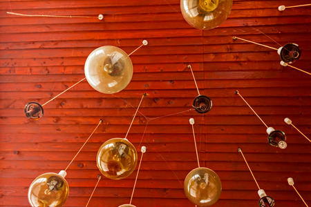disuse: Chandelier hanging from wooden ceiling on a long cable Stock Photo