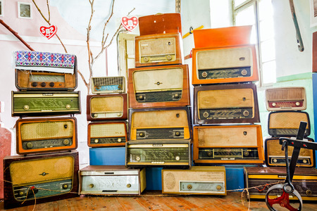 Collection of old wooden radios exposed in museum stacked one on the other