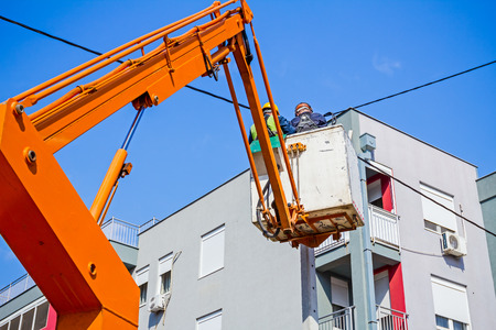 elevator operator: Technician works in a bucket high up on a power pole.