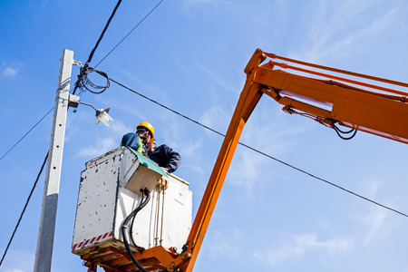 skilled operator: Technician works in a bucket high up on a power pole.
