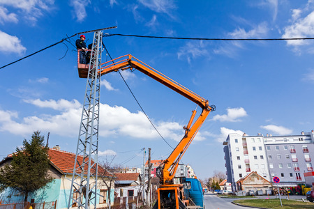 skilled operator: Technician works in a bucket high up on a power pole