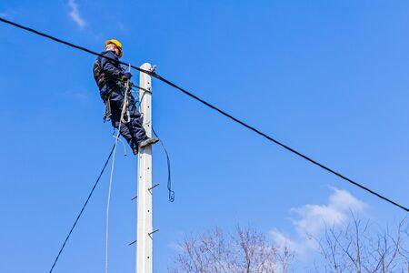 electricista: T�cnico trabaja en lo alto de un poste de electricidad