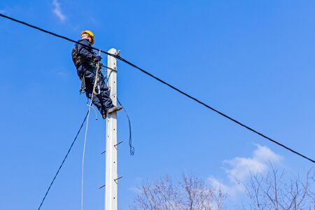 electricity pole: Technician works high up on a power pole