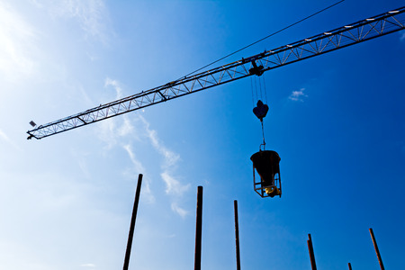 containment: Silhouette of industrial construction crane on a beautiful sky background