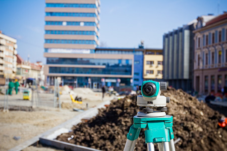 geodesist: Surveying measuring equipment level transit on tripod at construction building area site