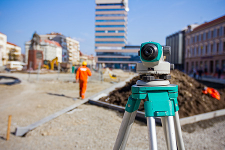 geodetic: Surveying measuring equipment level transit on tripod at construction building area site