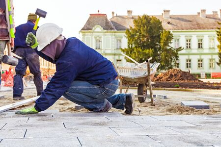 landscape stones: Workers stack paving block on city street