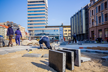 Workers stack paving block on city street