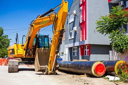 backhoe loader: Excavator loader with backhoe is standing over blue sky in city street