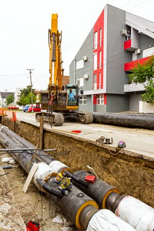Excavator holds pipeline above the trench during the welding procedure. 스톡 콘텐츠