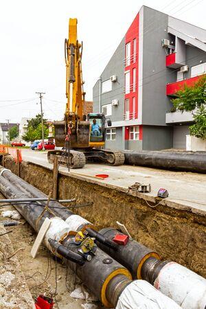 Excavator holds pipeline above the trench during the welding procedure. Standard-Bild