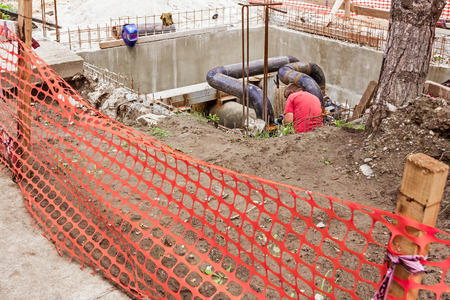 junction pipe: Orange fence around the construction site and metal worker is in a manhole