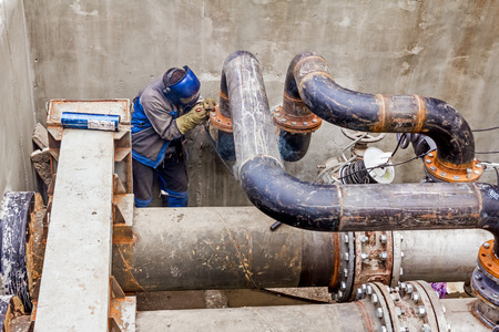 Welder is welding pipe junction completing a manhole for heating pipeline system Stock Photo