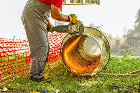 Industrial worker on construction site is grinding to cut a huge pipe wearing his protective glasses. Stock Photo