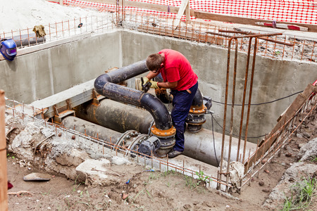 junction pipe: Metal worker is grinding weld on pipe junction completing a manhole for heating pipeline system.