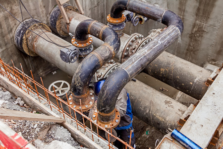junction pipe: Welder is welding pipe junction completing a manhole for heating pipeline system Stock Photo