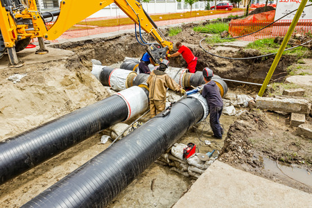Team of workers in trench working hard to install a new pipeline