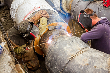 dirty environment: Two welders working on a pipeline in dirty environment