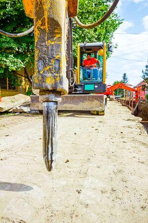 plugin: Excavator has attached hydraulic plug-in platform demolition hammer. Stock Photo