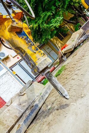 attached: Excavator has attached hydraulic plug-in platform demolition hammer. Stock Photo