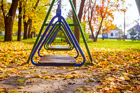 Empty chain swing with yellow leaves in park at autumn time photo