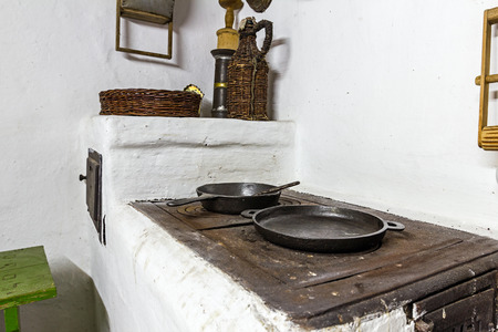victorian fireplace: Cooking in a frying pan on old stove at antique kitchen. Stock Photo