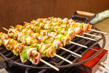 broiling: Grilled gourmand chicken skewers are made with white meat, bacon and pieces of green paprika being turned on the BBQ. Stock Photo