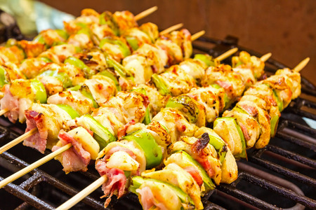 turned: Grilled gourmand chicken skewers are made with white meat, bacon and pieces of green paprika being turned on the BBQ. Stock Photo