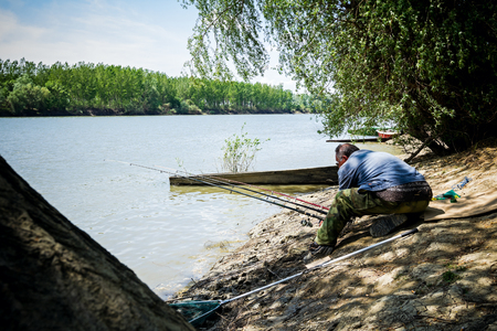 avocation: Man is fishing on the river at sunny day.
