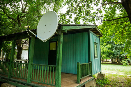 front stoop: Green camping cabin is made of wood with satellite dish on her roof. Stock Photo