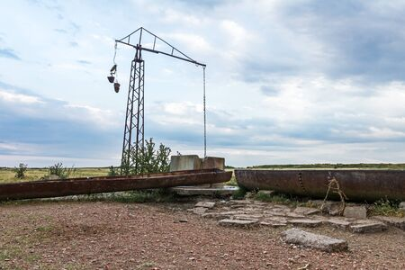 trough: Shadoof well is placed near the cattle trough on grass field.