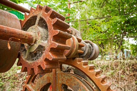 meshing: Detail of two gears meshing together as a part of rusty transmission. Stock Photo