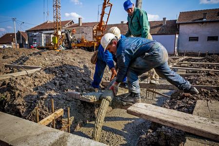operarios trabajando: Trabajadores de la construcción están vertiendo hormigón en la construcción de cimientos, dirigir el tubo de la bomba en la dirección correcta.